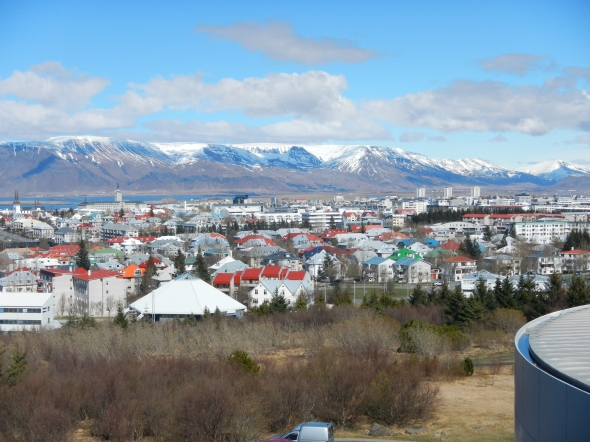 A view from Perlan's observation deck of the city and volcanic mountains.  Note the colorful buildings - there are no color regulations for painting homes and businesses, so the people of Iceland like to use a range of color, and much of it!