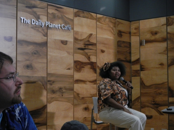 Dr. Danielle Lee, speaking on the mini-stage in The Daily Planet Cafe (with David Shiffman (@whysharksmatter) looking on from the left)