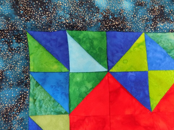 Close-up of blue and green batik fabrics included in the quilt I HeART Earth Science
