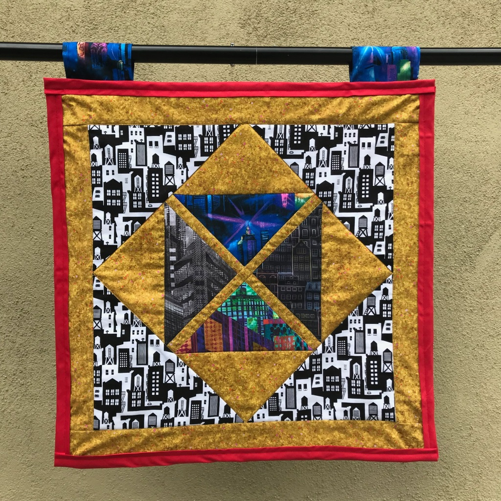 Source - Buildings Sector. Completed June 3, 2021, measures 21.5 inches by 21.5 inches. Based on a failed Falling Triangles design from Missouri Star Quilt Company.