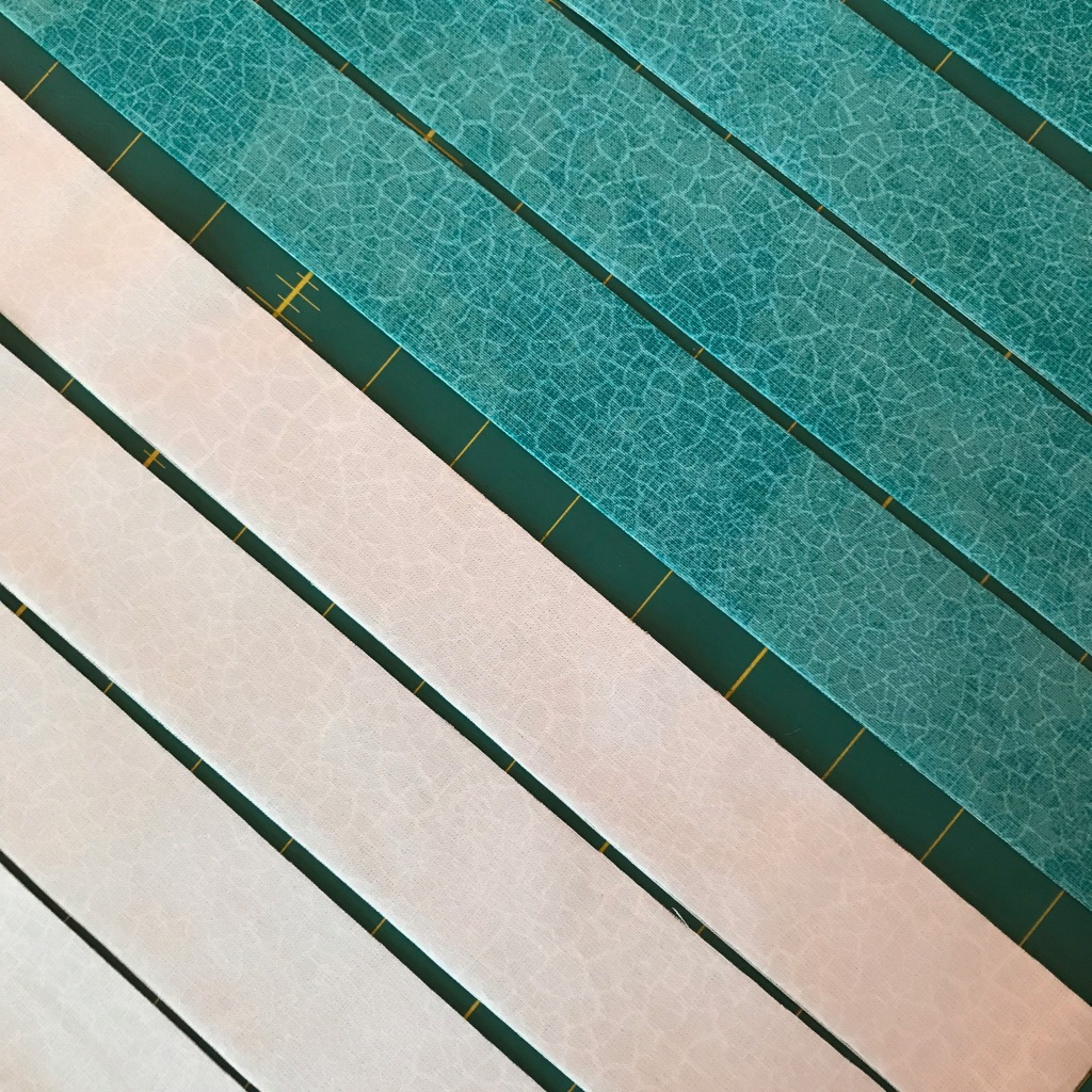 Diagonal strips of white and turquoise fabric